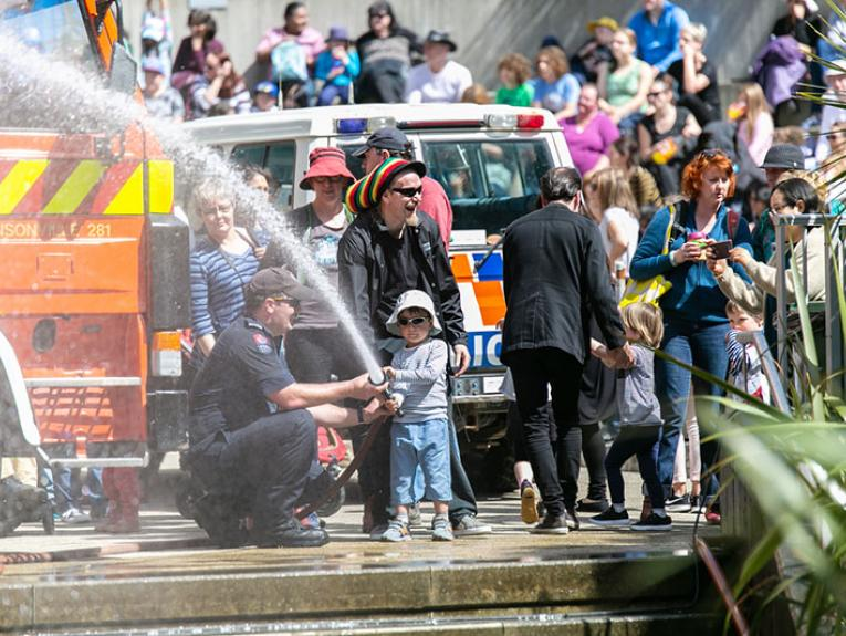 A young boy shoots a firehose into the air. There is large crowd in the background