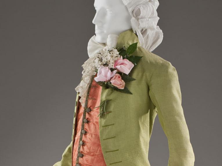 Men's jacket and breeches in a shiny green material, underneath is a shiny orange waistcoat