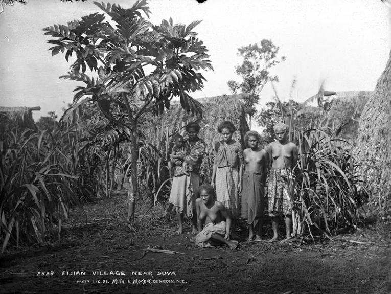 A black and white photo of a group of people stood under trees