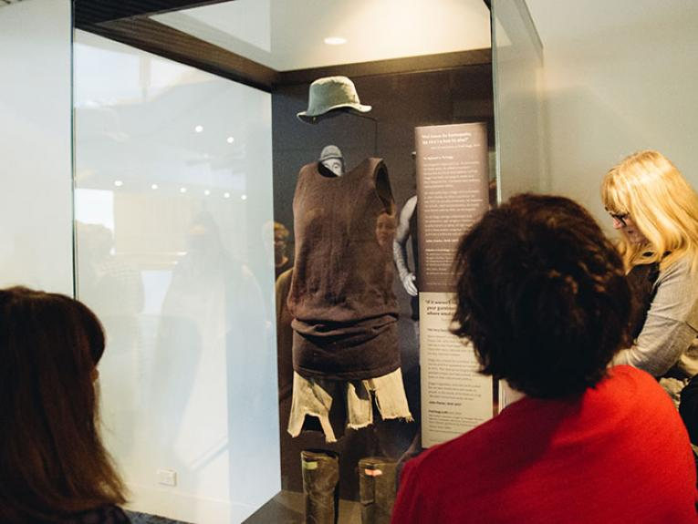 People look at the Fred Dagg costume - hat, singlet, shorts, and gumboots - in a display case