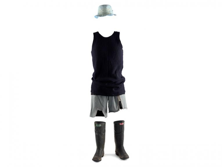 Gumboots, shorts, a singlet and a hat set up like there is a person wearing them on a white background