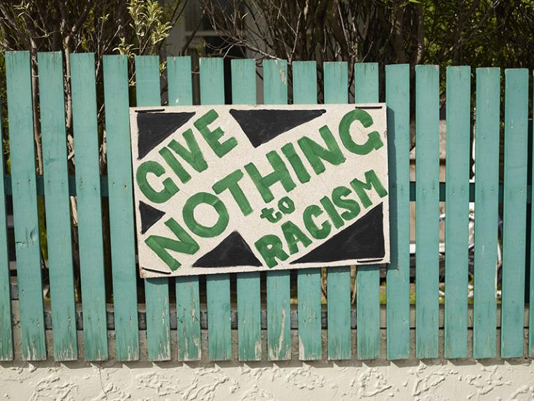 Green fence with a hand-painted sign on it saying, 'Give nothing to racism' in green and black.