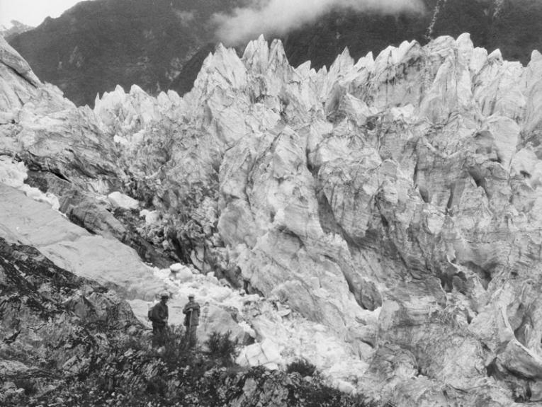 Two men next to craggy ice