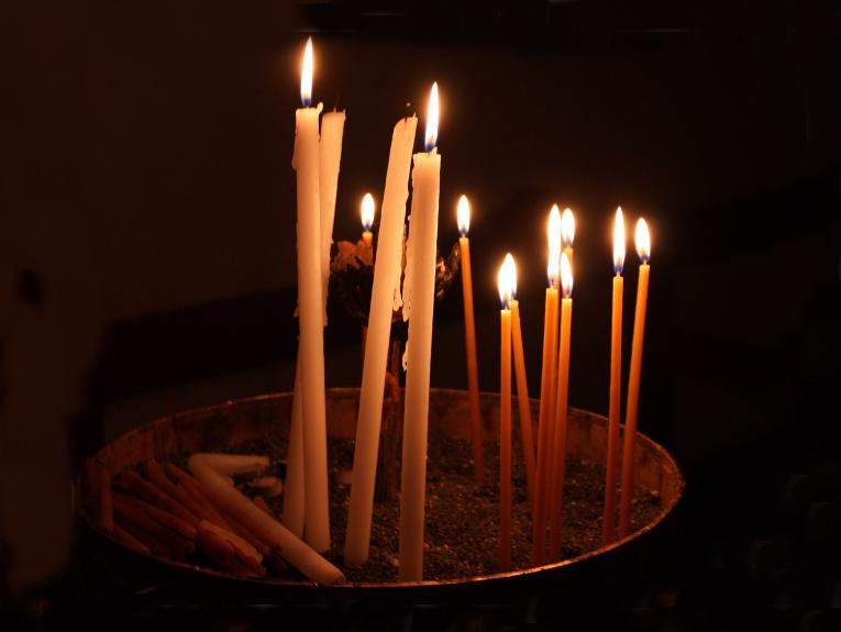 Several thin candles lit in a dark space