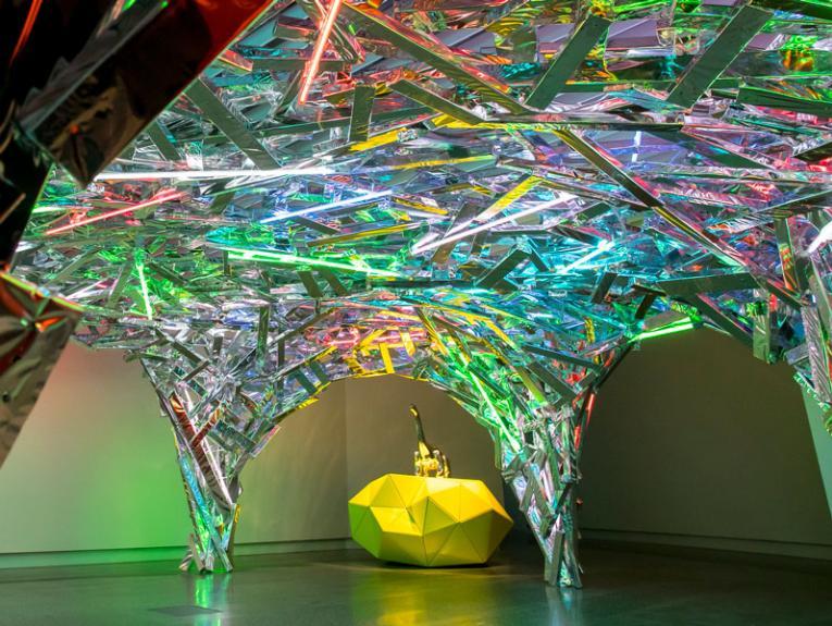 A shiny colourful artwork featuring a metal dinosaur