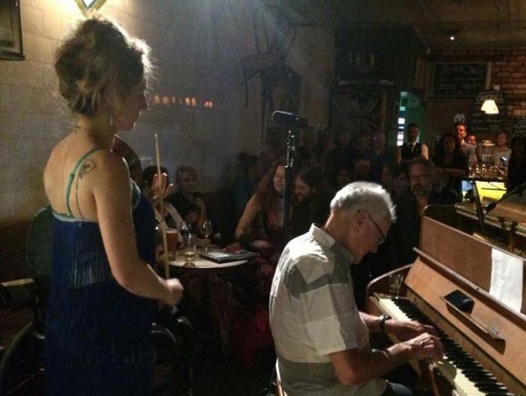 HaRRY playing a gig in a bar. A man plays the piano and a lady stands with her violin