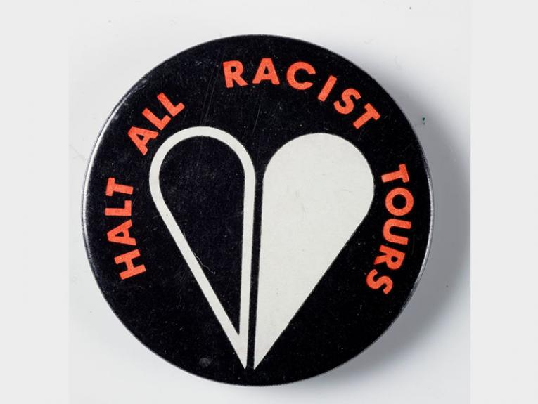 a round badge with a heart on it, half in black, half in white. Orange text around the outside saying 'Halt All Racist Tours'.