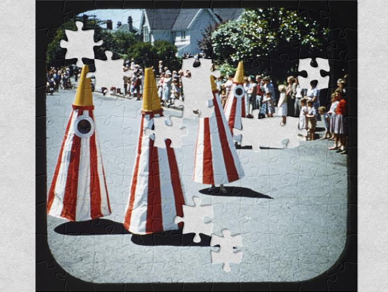 Four people in cone costumes in a parade. Many people lining the street in the background