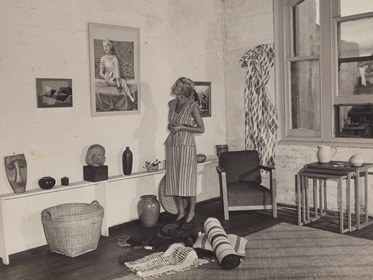Helen Hitchings inspecting a self-portrait on display in her gallery