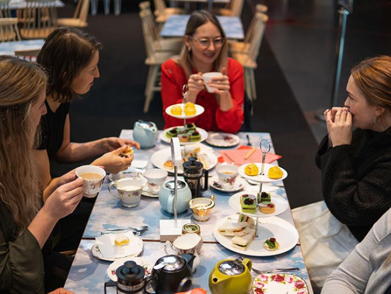 A group of people sit around a table eating small foods and drinking tea