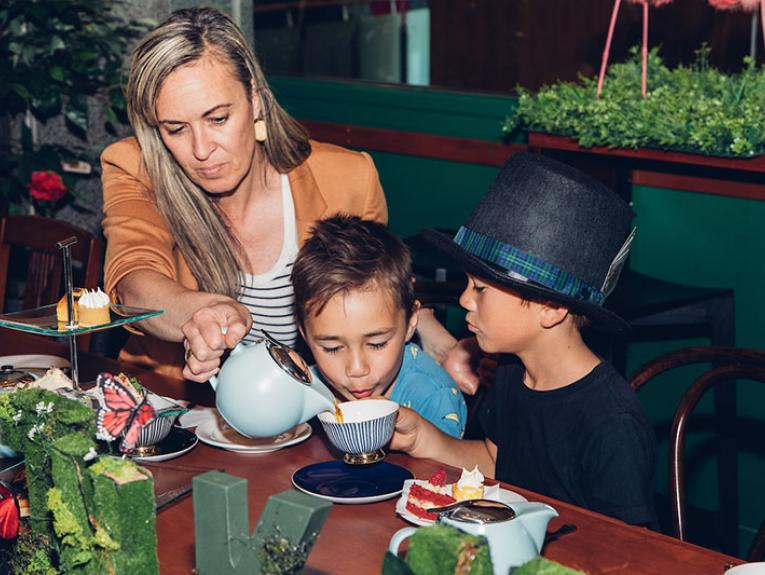 A woman pours a cup of tea for two children at a table