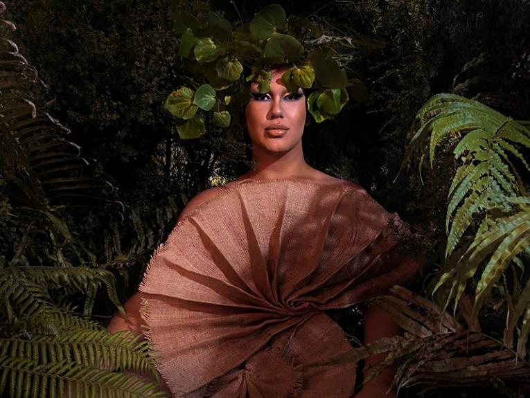 A person in costume surrounded by leaves