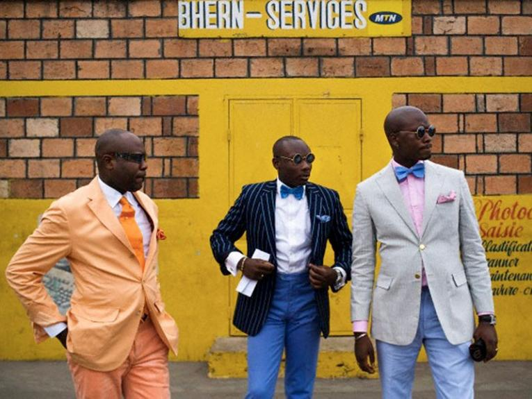 Three men in colourful suits and sunglasses stand in front of a building heavily painted in bright yellow