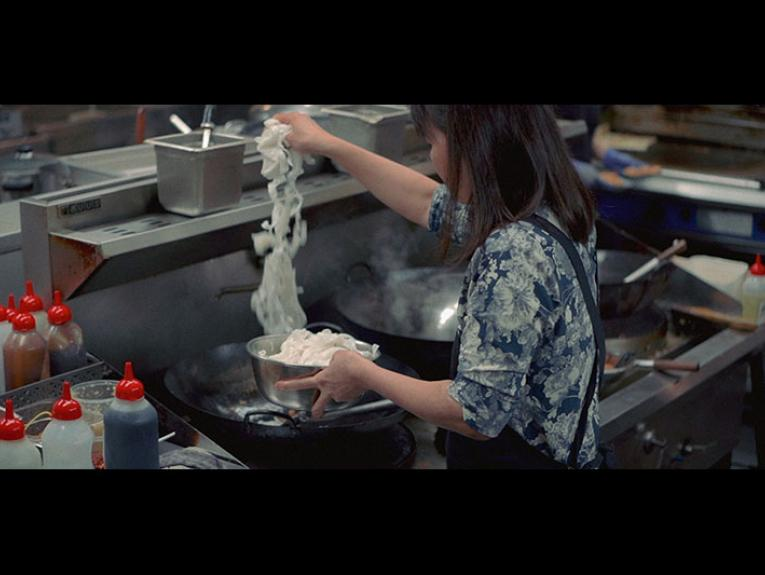 A woman is seen from behind putting noodles into a wok in a busy kitchen