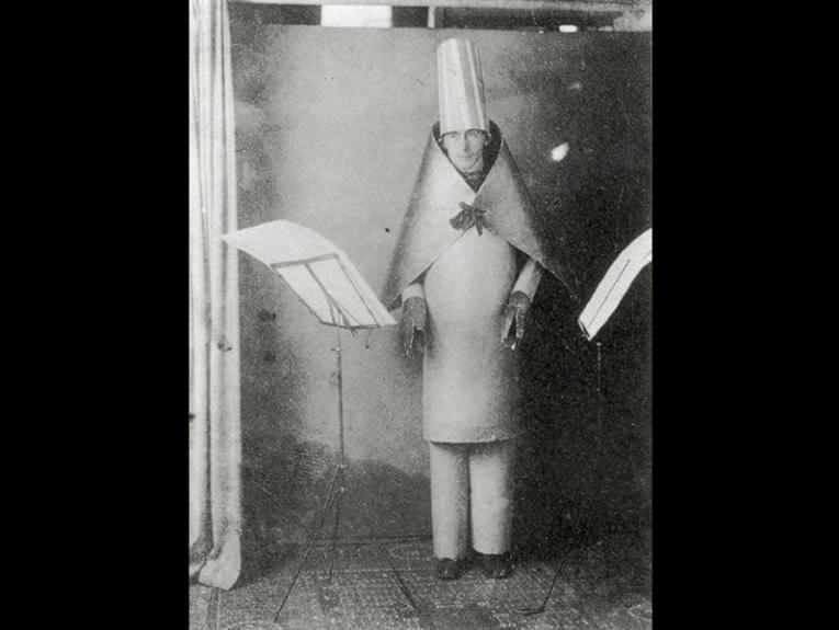 An old black and white photo of a man dressed in cardboard cones on his body and his head, with a large page on a music stand to his right