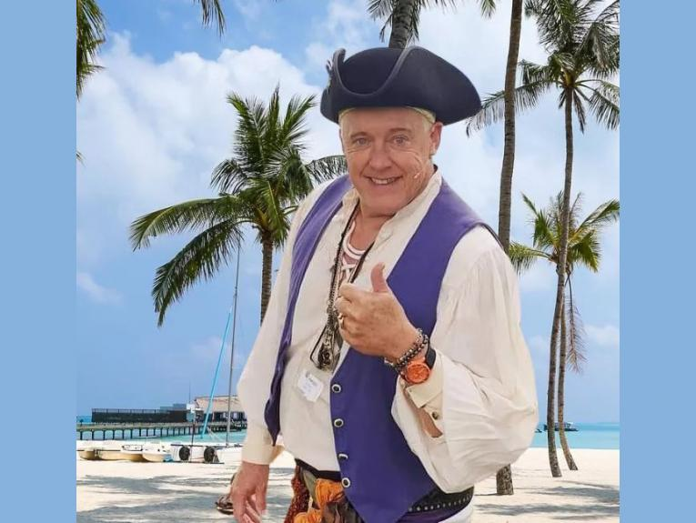 Zappo dressed as a pirate on a beach with palm trees and a bay behind him