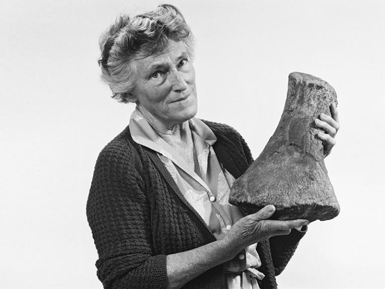 A black and white photo of an older woman holding up a fossil