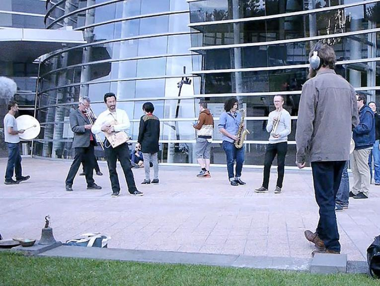 Musicians perform scattered about outside a building