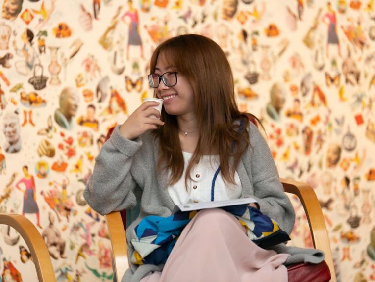 A lady drinks tea in an art exhibition space