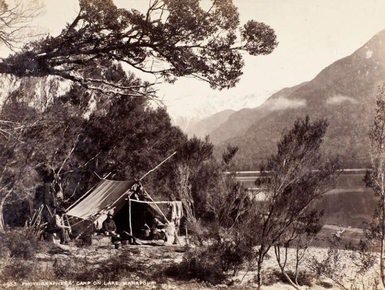 Black and white photograph of a camp beside a lake