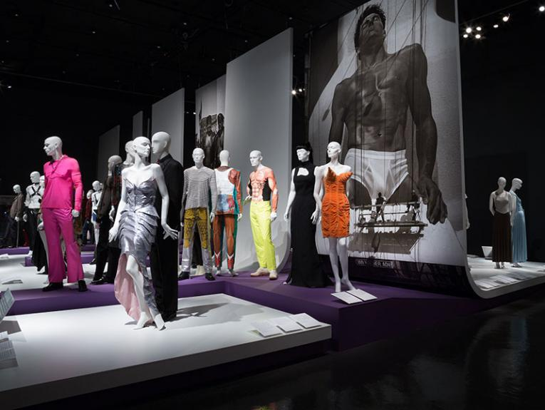 Mannequins in various colourful dresses and clothing are on stage with massive pictures of peaople on the wall behind them