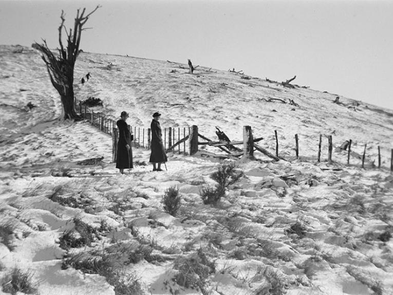 Two women in formal coats and hats stand for a photo in a field covered in snow, beside a fence