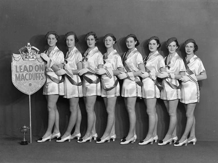 Black and white photo of eight women in matching uniform lined up with a sheild