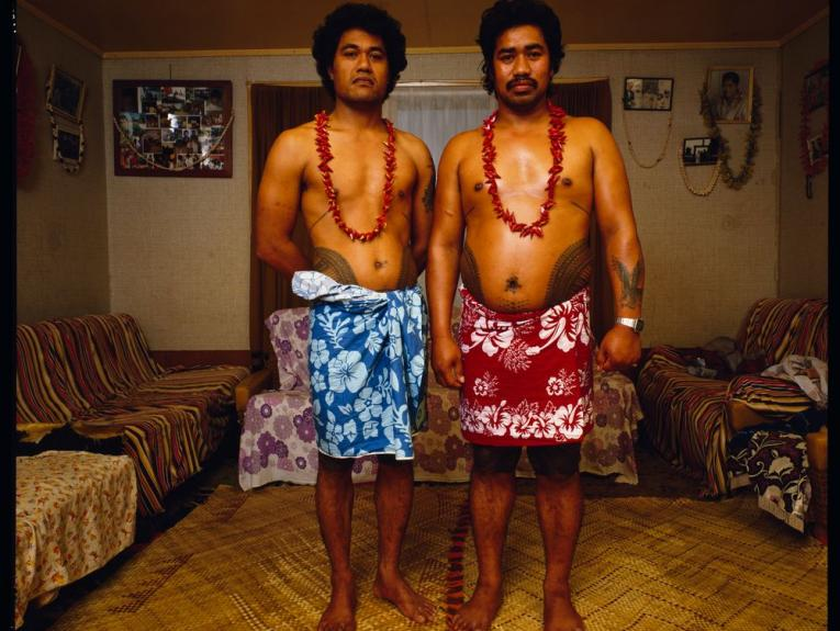 Two Sāmoan men in lavalava's standing in a living room looking at the camera