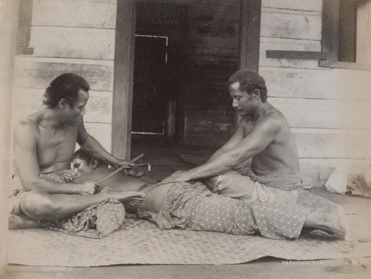 A sepia photo of two Sāmoan men tattooing another man who is lying down on a flax mat