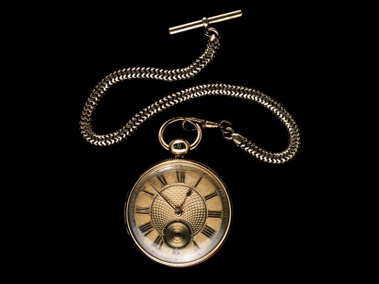 A pocket watch and chain on a black background