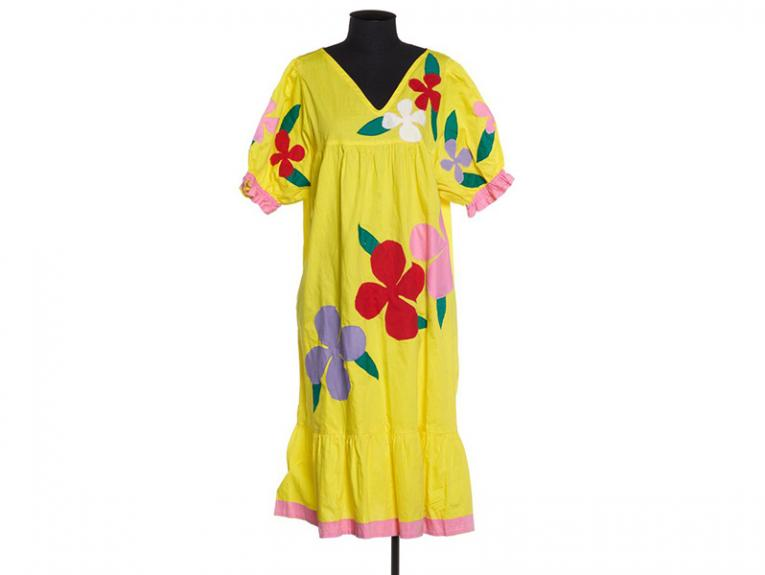 A yellow dress with large red flowers on a clothmaker's dummy