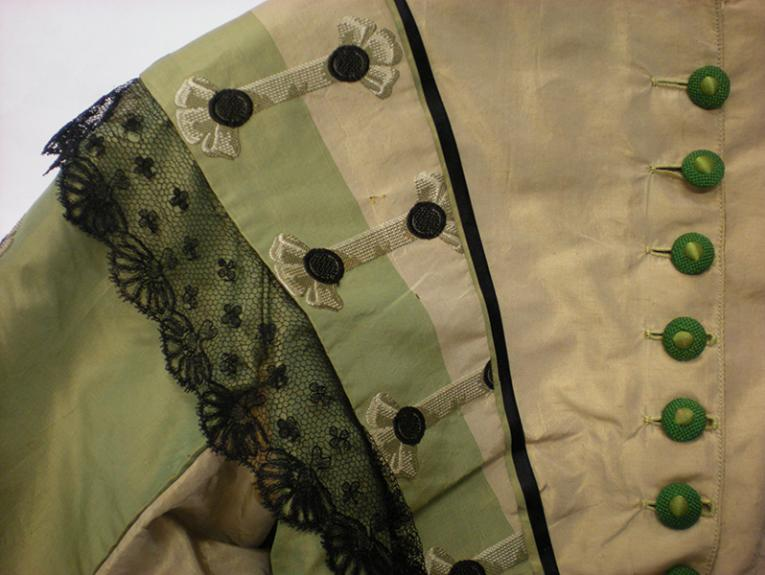 a close up image of the should of a green and cream Victorian bodice