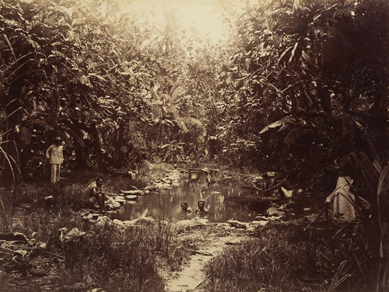 A sepia photo of people in a pond with another person standing next to them