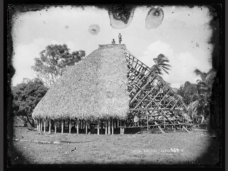 Several unidentified men are standing on the framework of a partially-thatched faletele, grass in foreground and trees and palms in the background