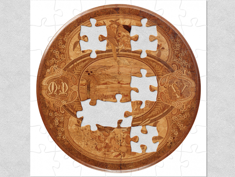 A circular wine or card tabletop with wooden marquetry made from indigenous New Zealand timbers