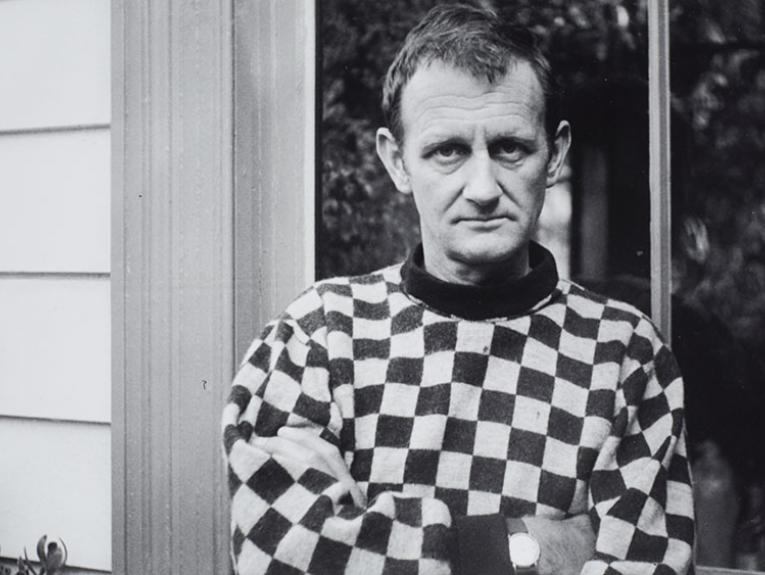 Colin McCahon stands outside a house in front of a large window, wearing a checkered shirt, with his arms folded