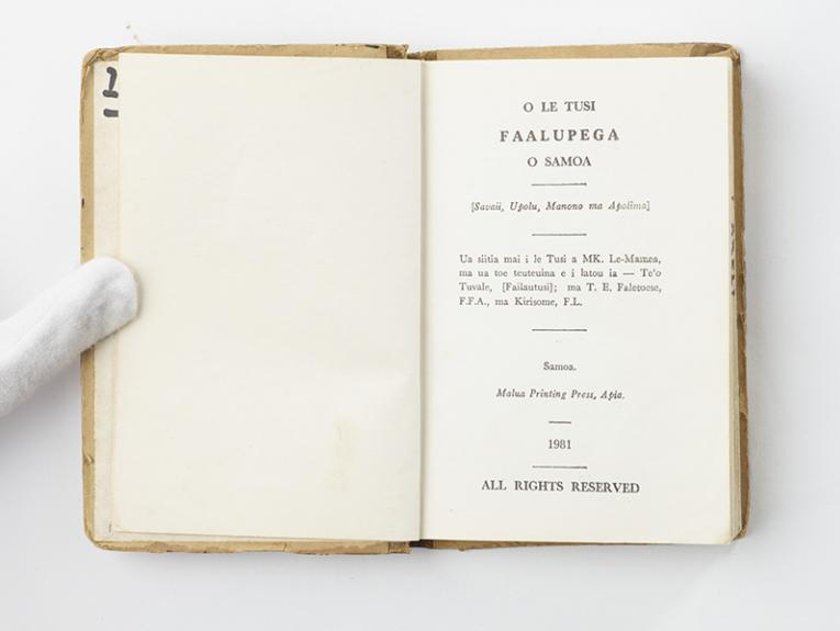 An open book with Sāmoan text printed on the page