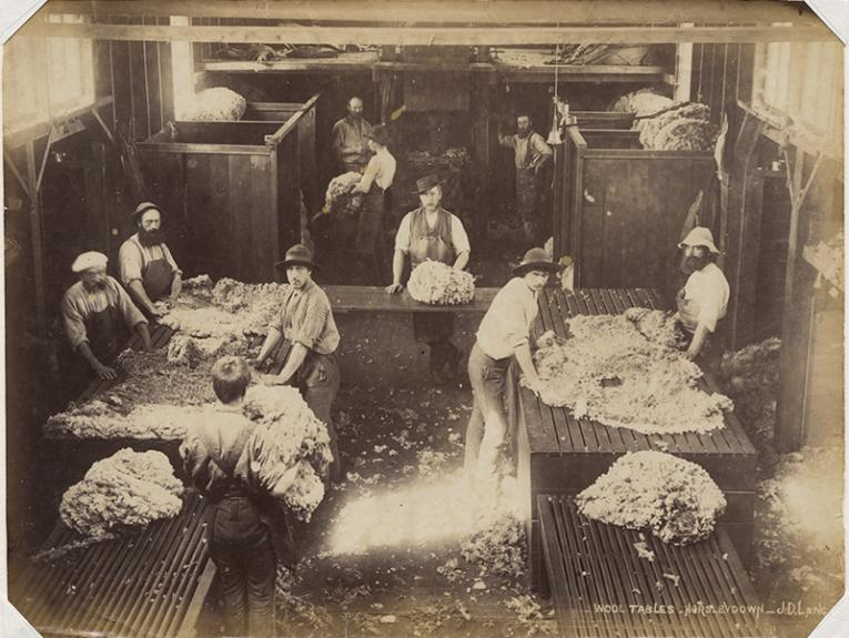 A sepia photo of a woolshed with ten people surrounding big tables with shorn wool sitting on them