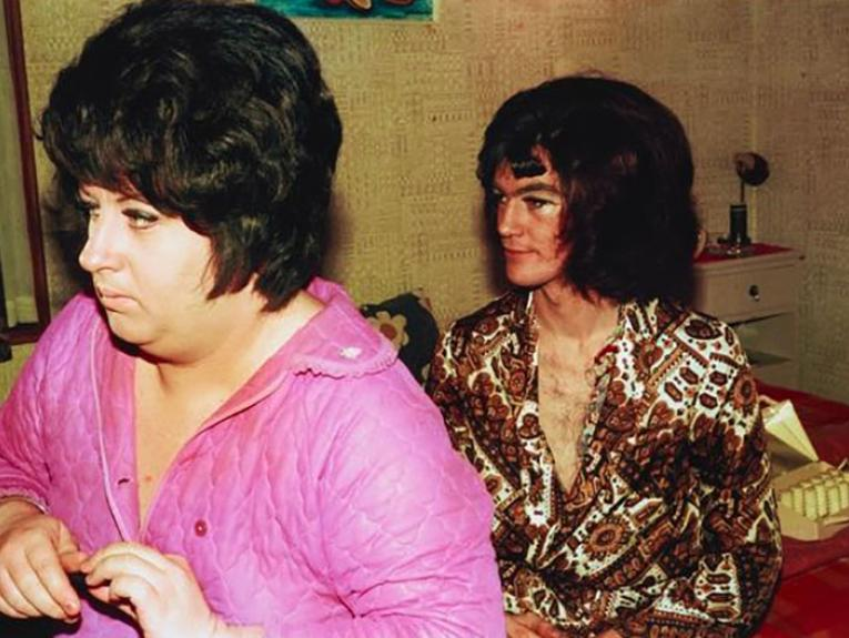 Two men, wearing wigs, sitting on a bed get dressed. One wears a pink blouse and the other a brown shirt