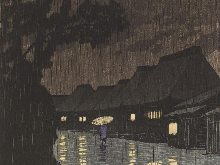 Person walks down a path in heavy rain, flanked by very tall trees on the left and houses with their lights on to the right