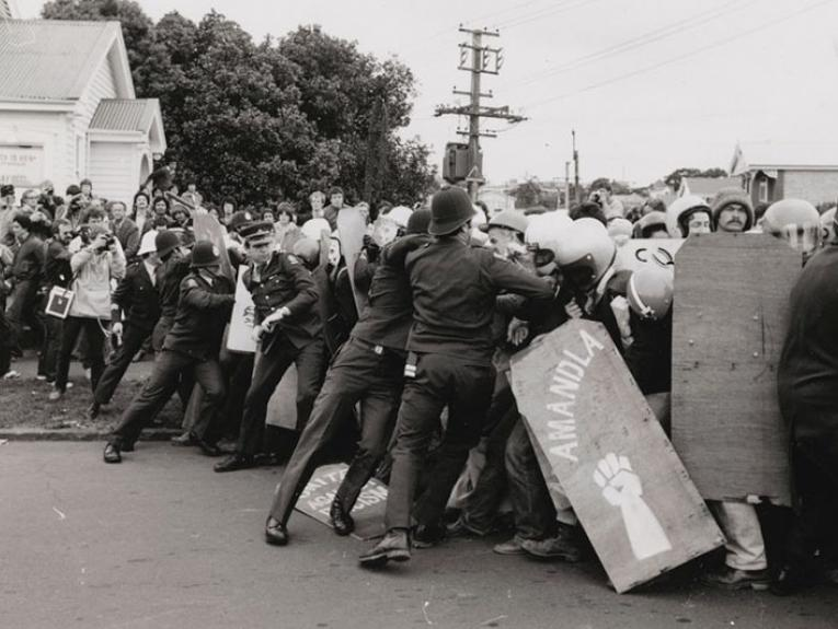 A scene of confrontation between a large group of protestors and the police