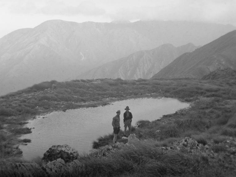 Black and white photo of two people standing next to a lake in the mountains