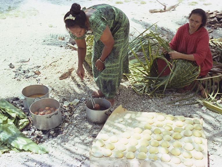 A woman prepares bread to fry in a pot, while another woman weaves with flax. They are sitting on a beach