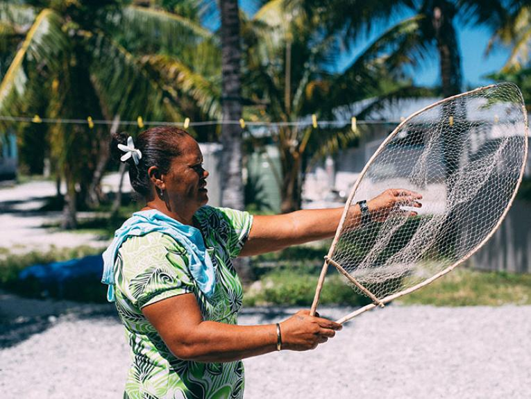 Woman holds a fishing net. Behind her is a house and palm trees