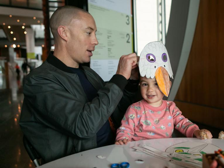 A father and son make bird masks