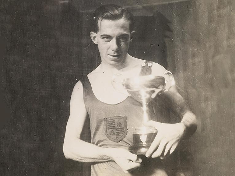 A man holds a trophy - dressed in 1930s sports gear