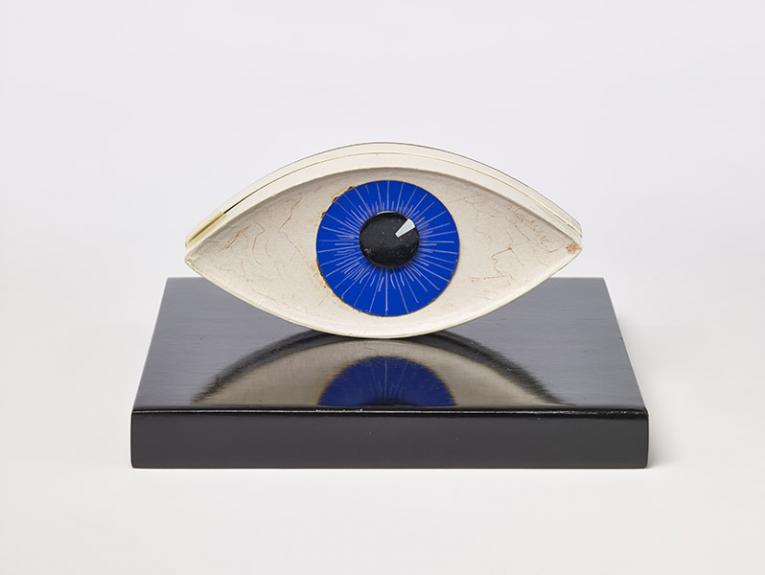 A sculpture on an eye on a black stand, the eye is blue and has red veins in the white area.