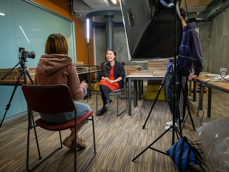 A woman sits on a chair in the middle of a room, being interviewed by another woman sitting opposite her. A large light shines on the subject