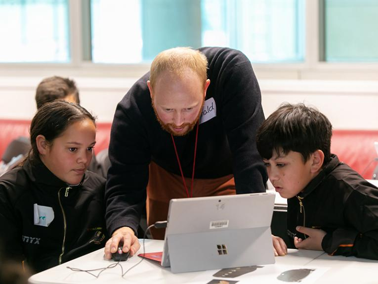 A man is showing something on a laptop device to two children