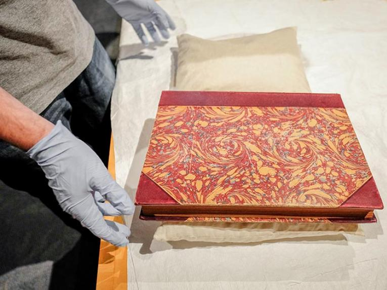 Librarian Martin Lewis with one of the rare books with a marbled cover